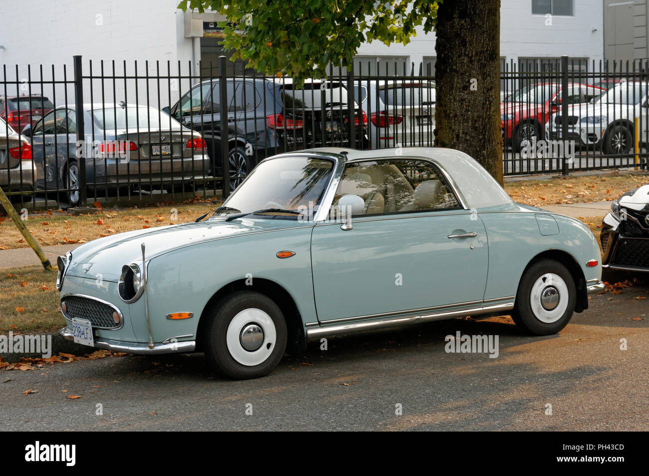Nissan Figaro 2+2 retro-styled fixed profile convertible car parked on a street in Vancouver, BC, Canada - Stock Image