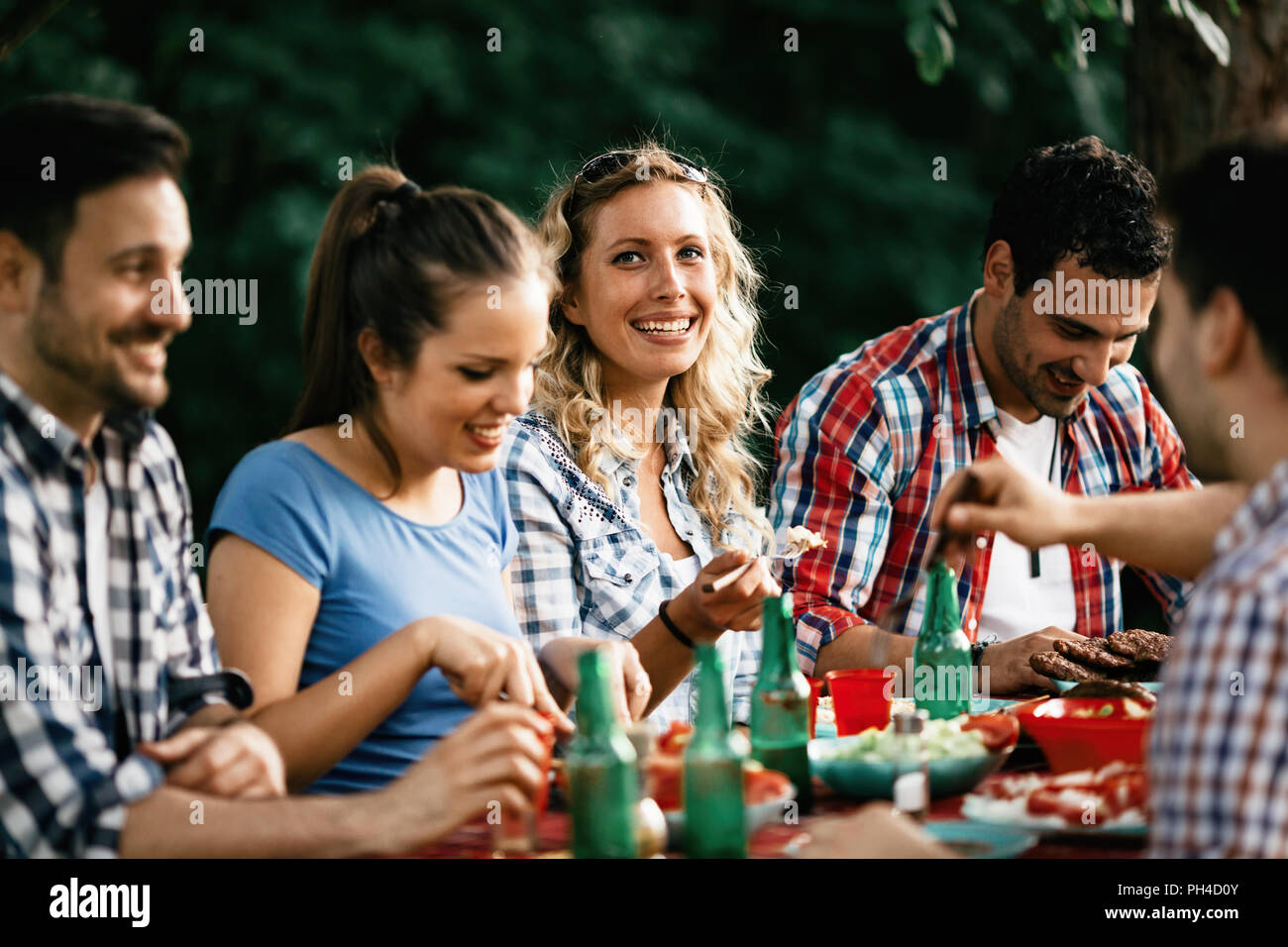 Group of happy people eating food outdoors - Stock Image