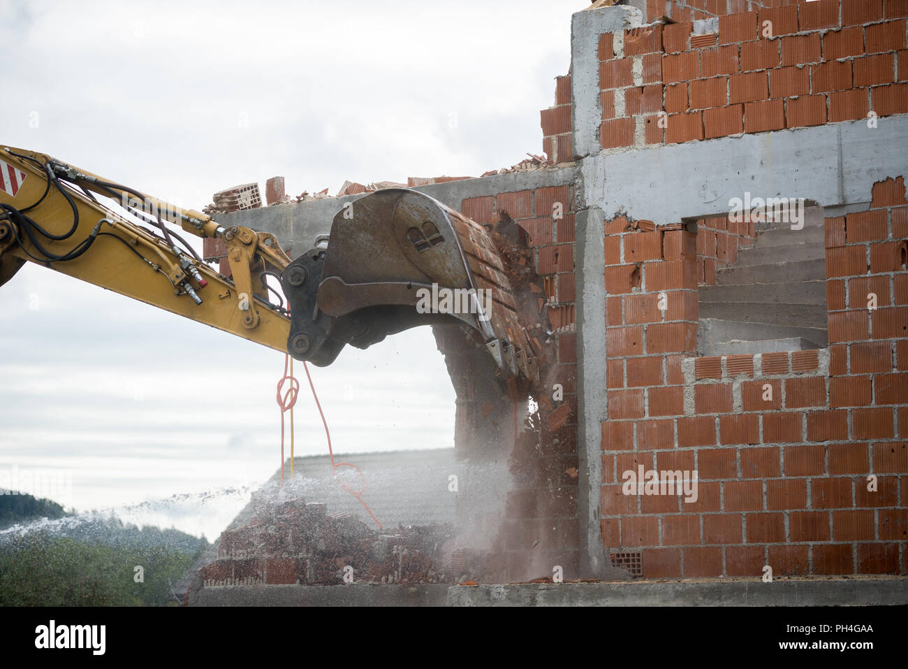 View of the hydraulic arm and bucket of a large heavy duty backhoe demolishing a brick house breaking down the exterior wall for removal. Stock Photo