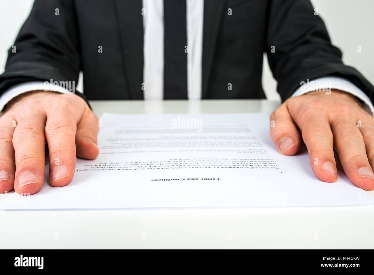 Close up low angle view of the hands of a businessman reading a document or contract resting on either side of the page with focus to the text Terms a - Stock Image