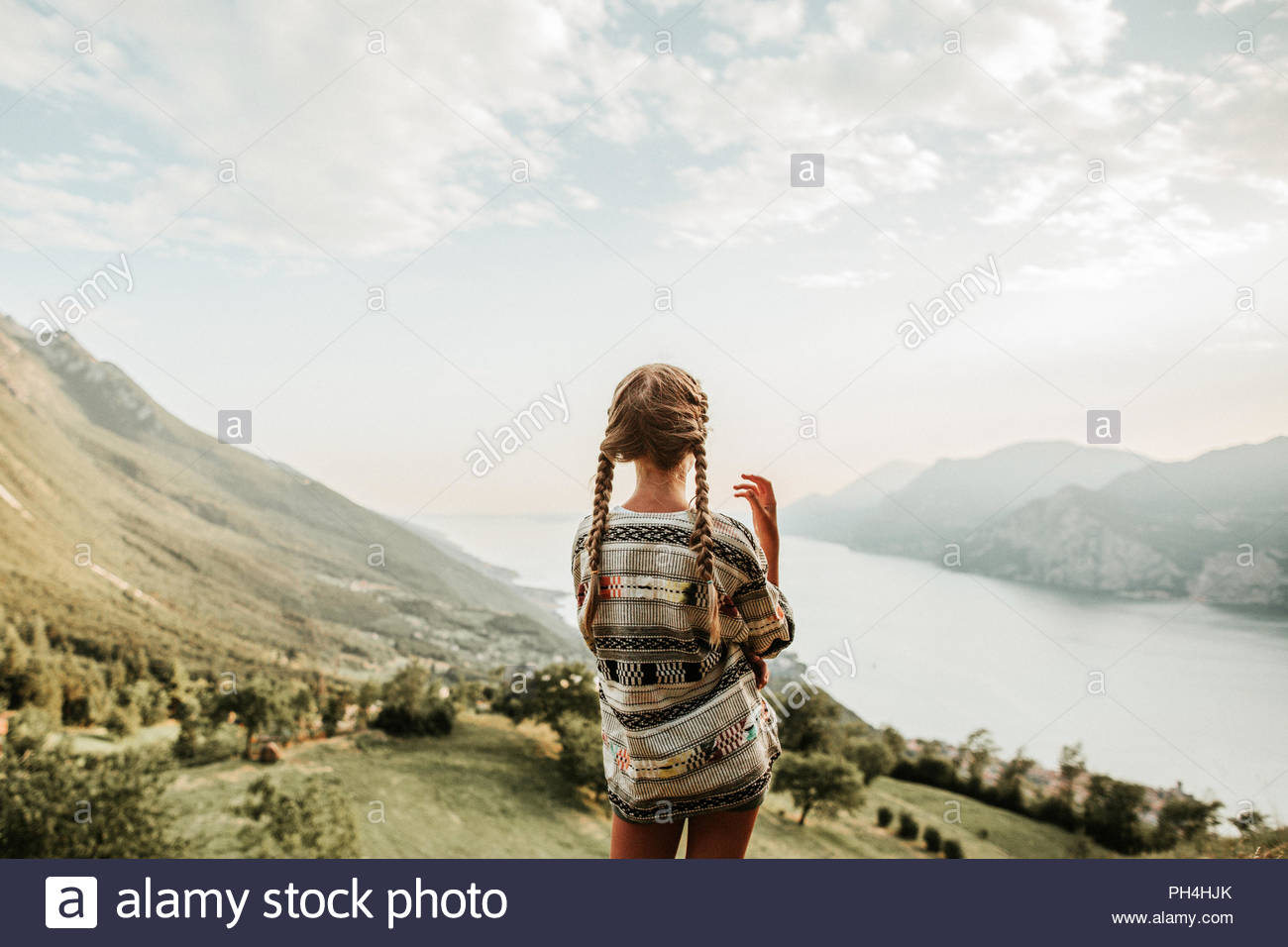 Rear view of a girl with pigtails on a hill at Lake Garda in Italy - Stock Image