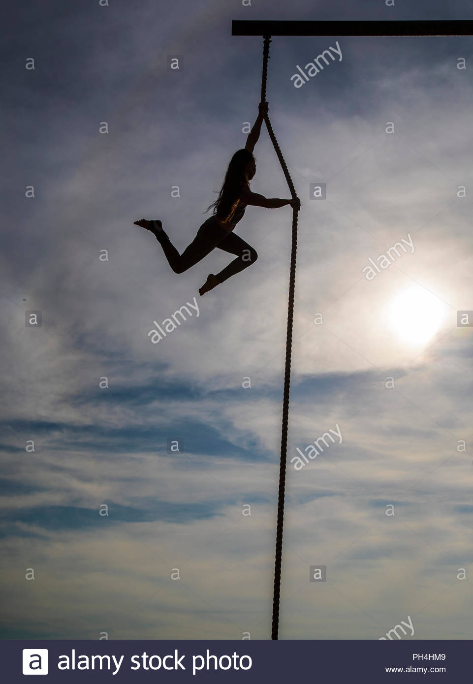 Silhouette of woman swinging on rope - Stock Image