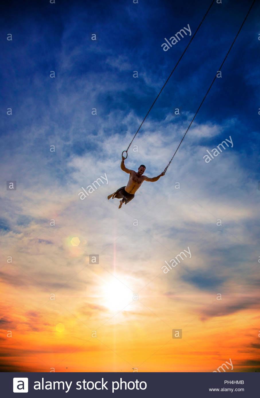 Man swinging on gymnastic rings during sunset - Stock Image