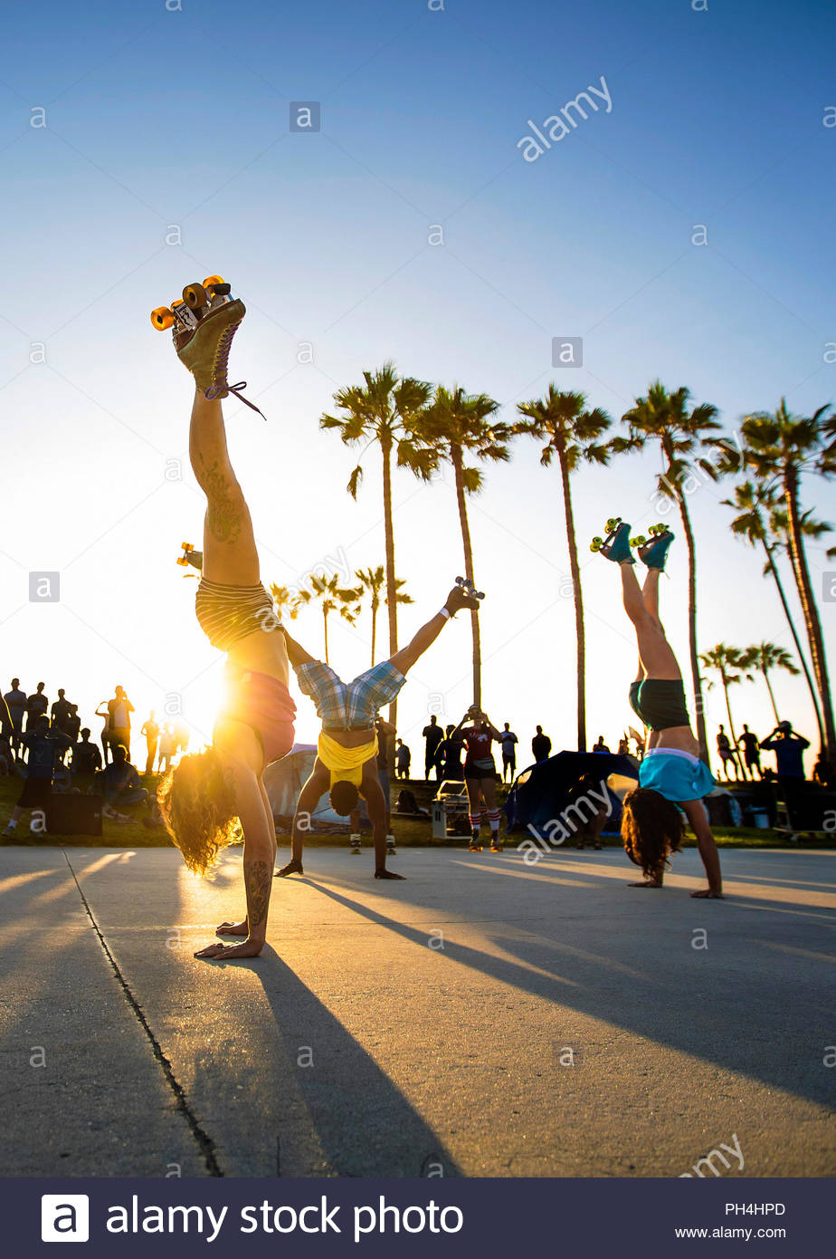 Group of women in roller skates doing handstands at sunset - Stock Image