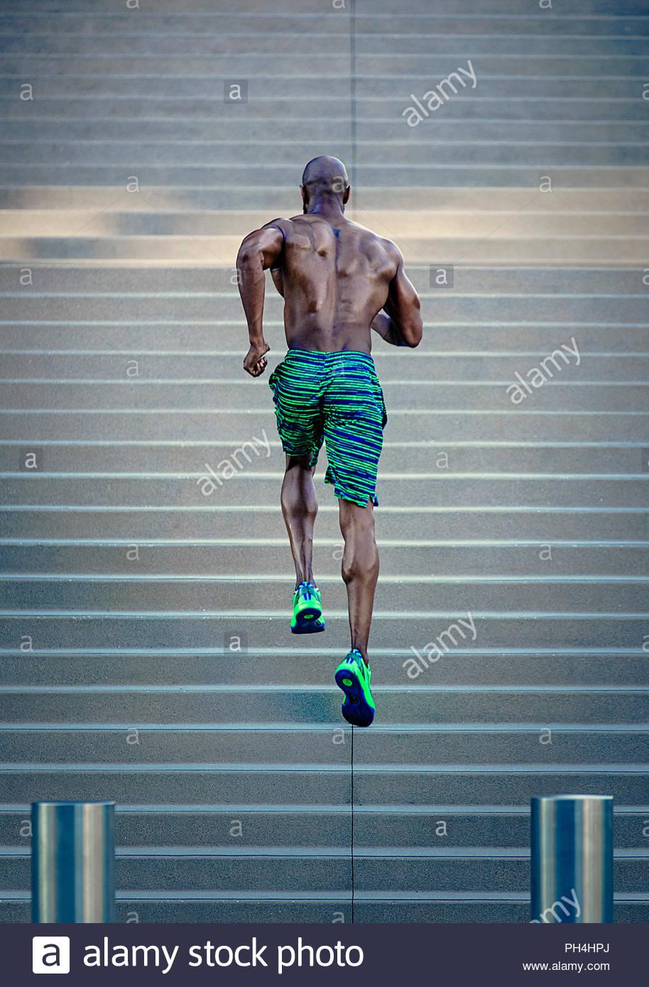 Shirtless man running up steps - Stock Image