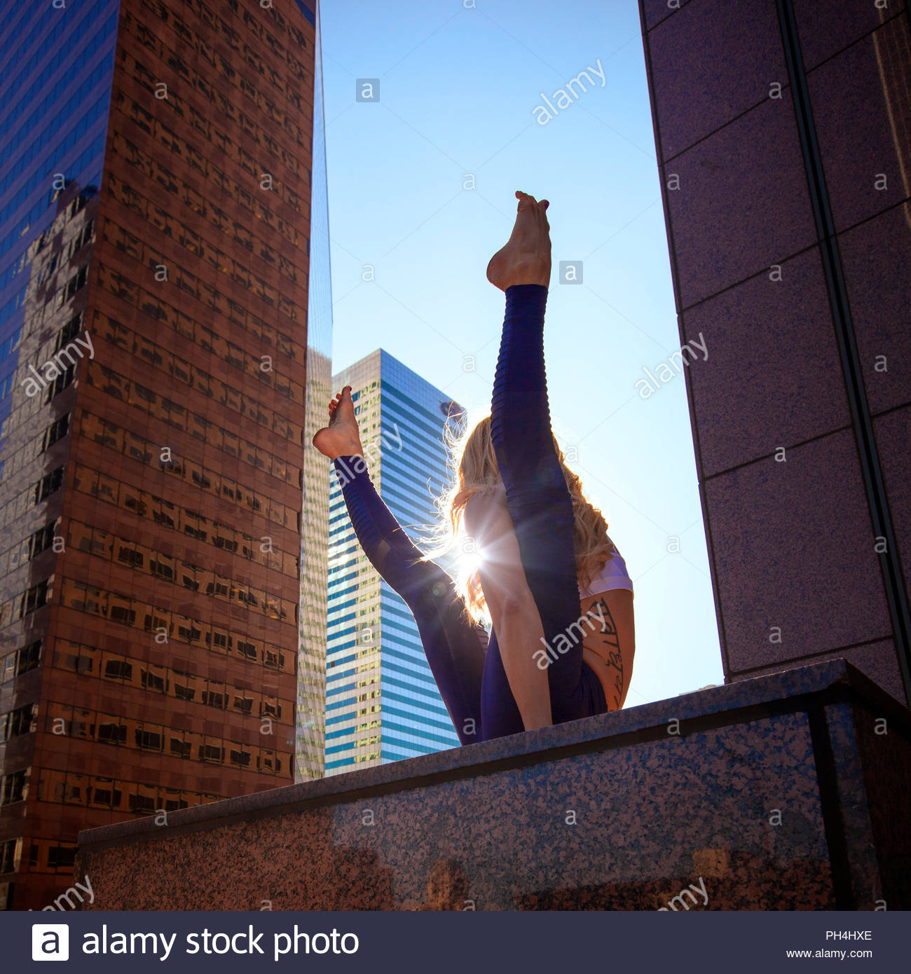 Young woman doing yoga on city rooftop - Stock Image