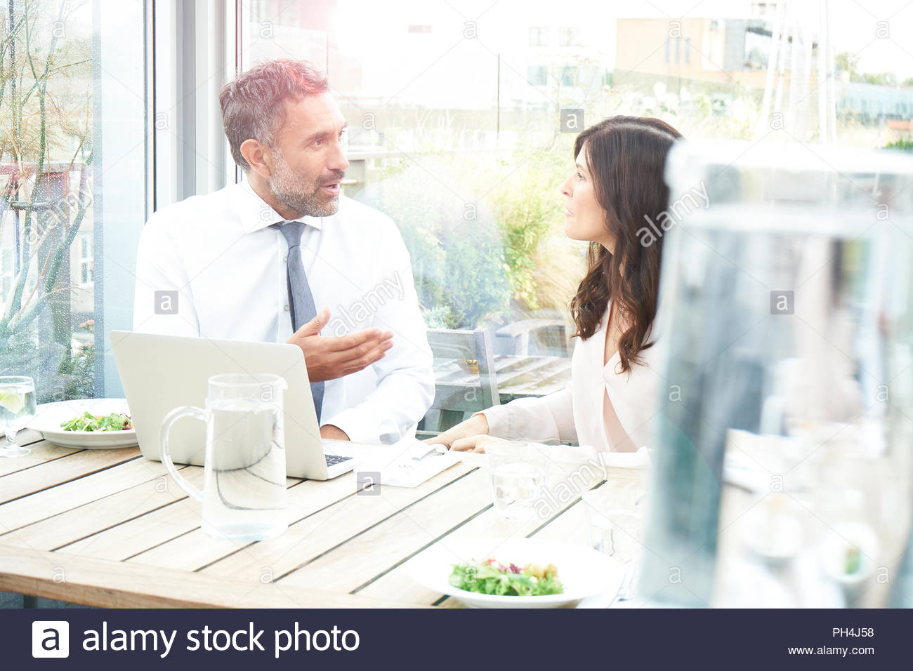 Businesspeople with a laptop at a restaurant meeting - Stock Image