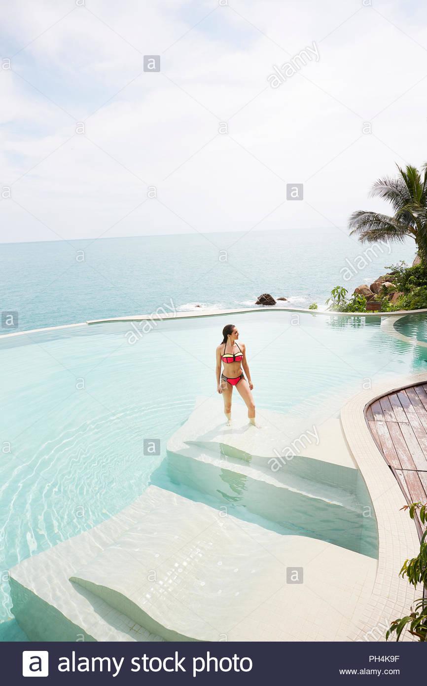 Young woman wearing red bikini in swimming pool - Stock Image
