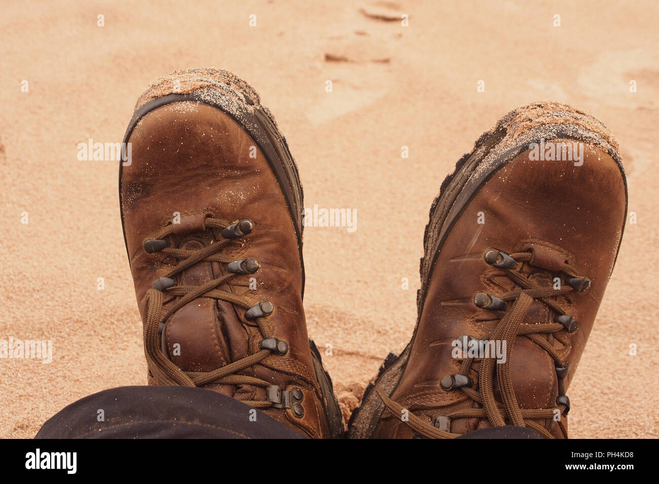 A close up of a pair of well used walking boots being worn on a sandy beach with sand stuck to the front edges - Stock Image