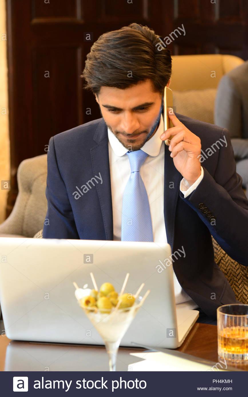 Businessman talking phone call at bar - Stock Image