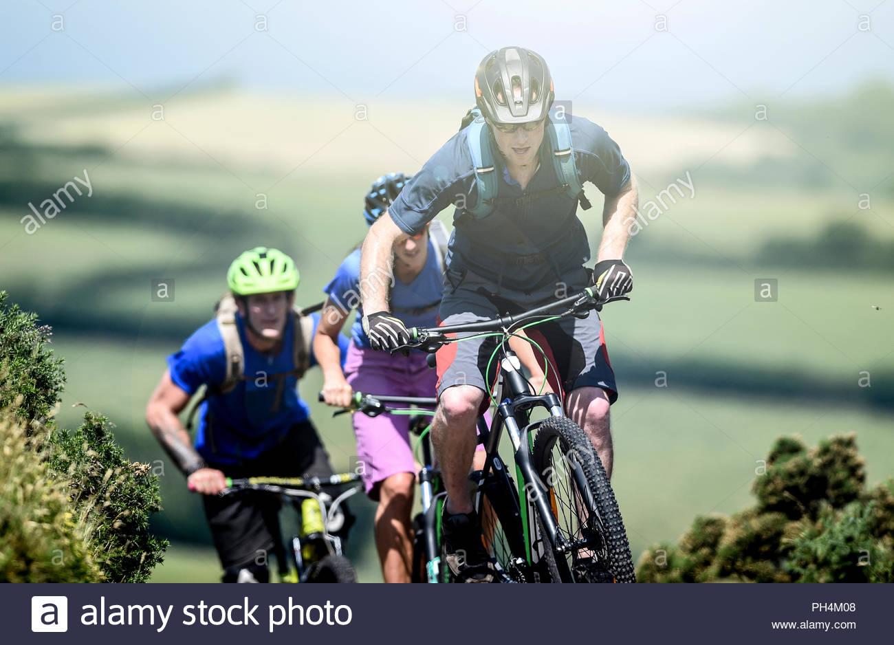 Friends mountain biking in Porlock Weir, England - Stock Image