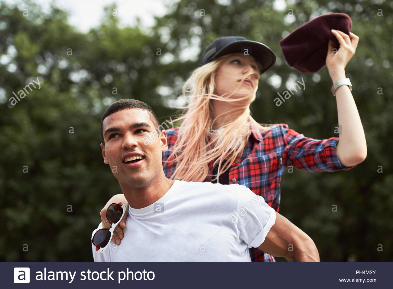 Teenage boy giving teenage girl piggyback ride - Stock Image