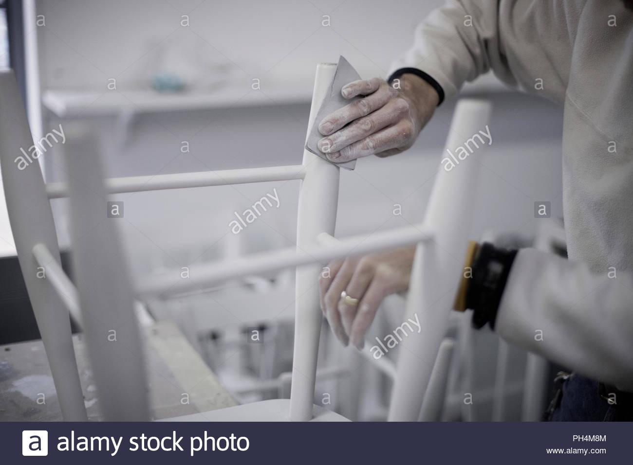 Man sanding stool - Stock Image