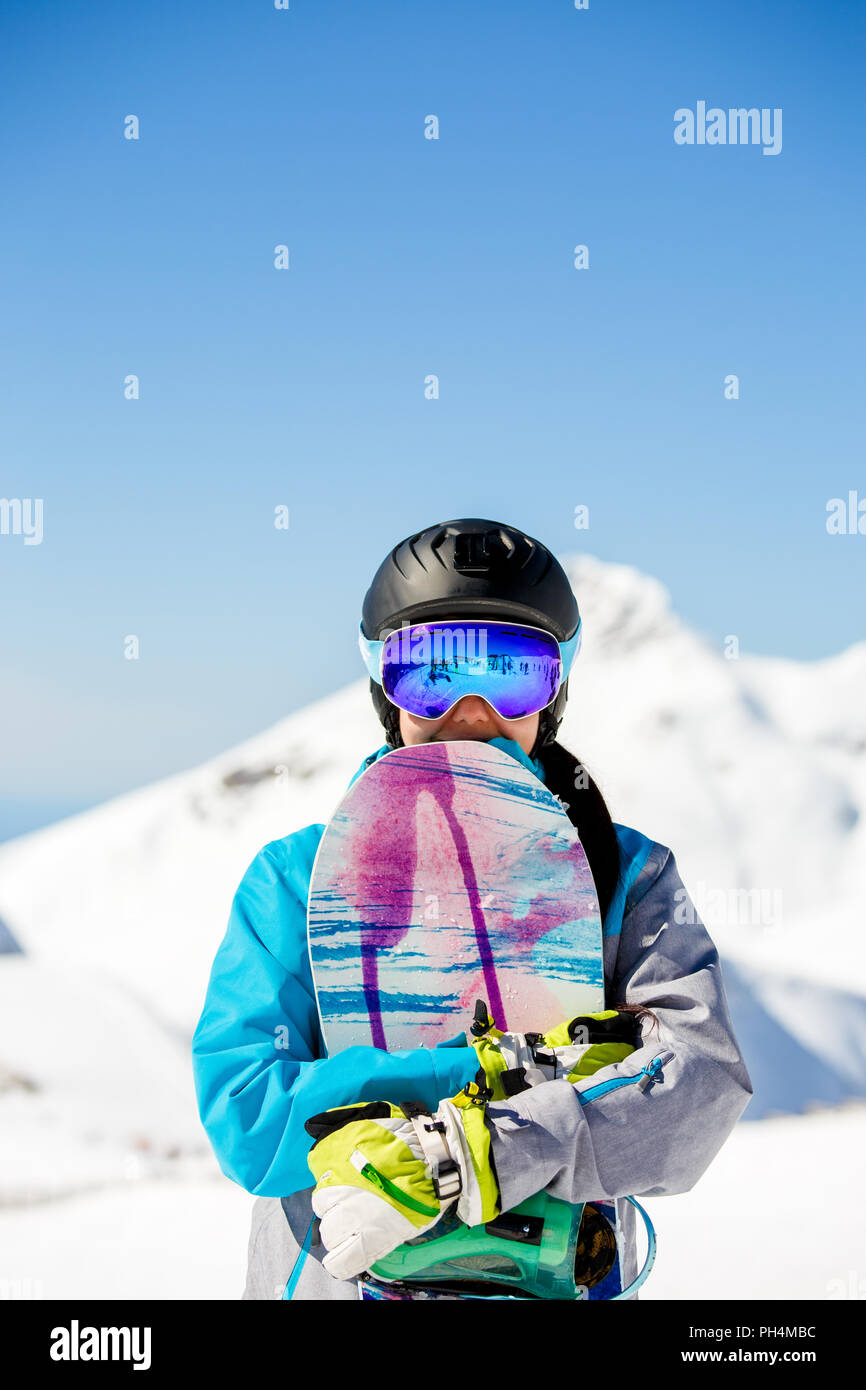 Photo of young tourist girl in helmet looking into camera with snowboard in  hands on background of snow mountains dc5281c76
