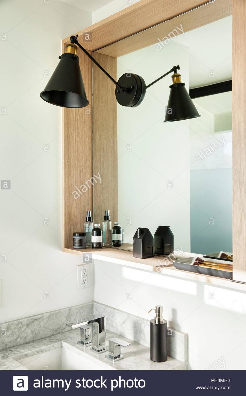 Lamp on mirror in bathroom - Stock Image