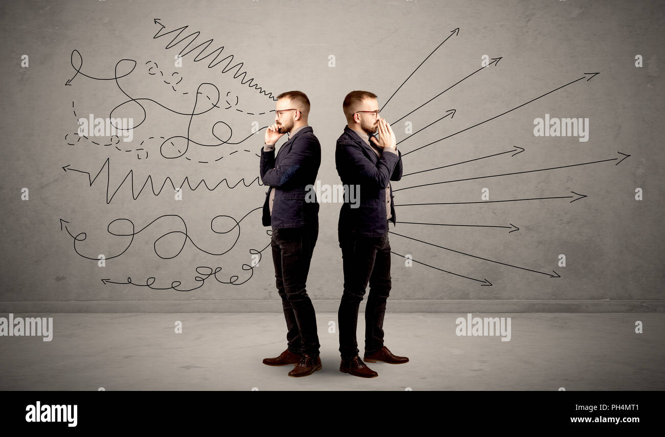 Young conflicted businessman choosing between two directions with arrows and scribbles around him - Stock Image