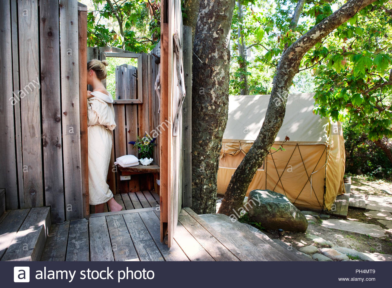 Woman wearing robe in outdoor shower - Stock Image