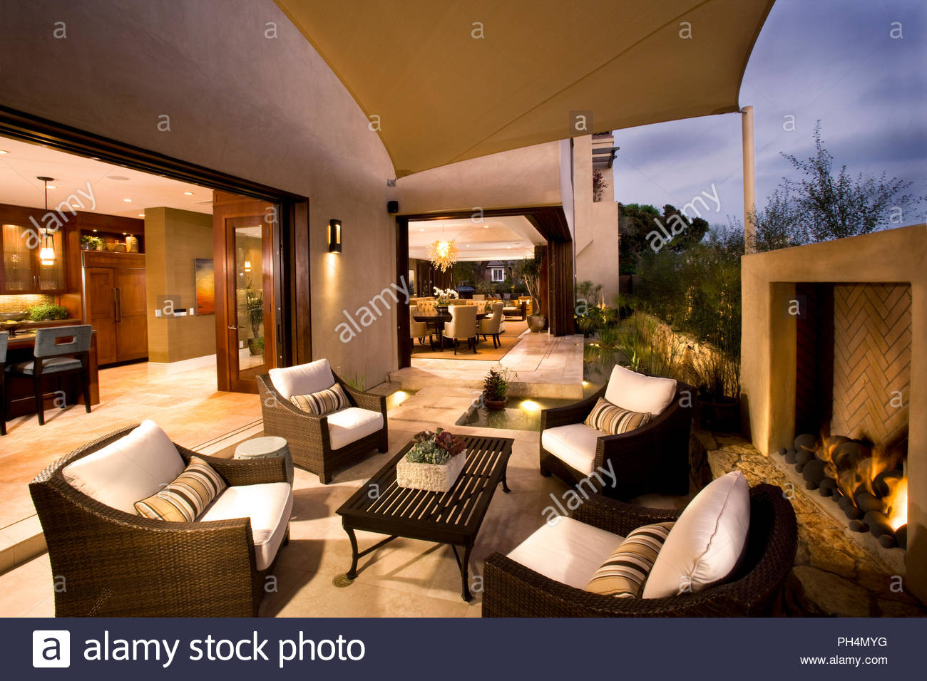 Outdoor chairs by fireplace on patio - Stock Image
