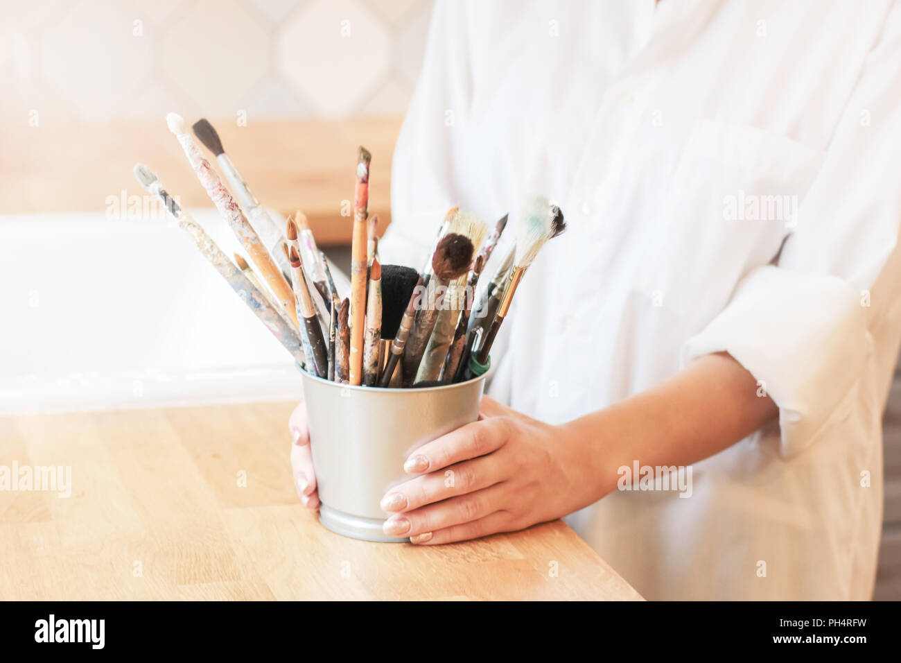 Different brushes in metal bucket with artist hands, selective focus Stock Photo