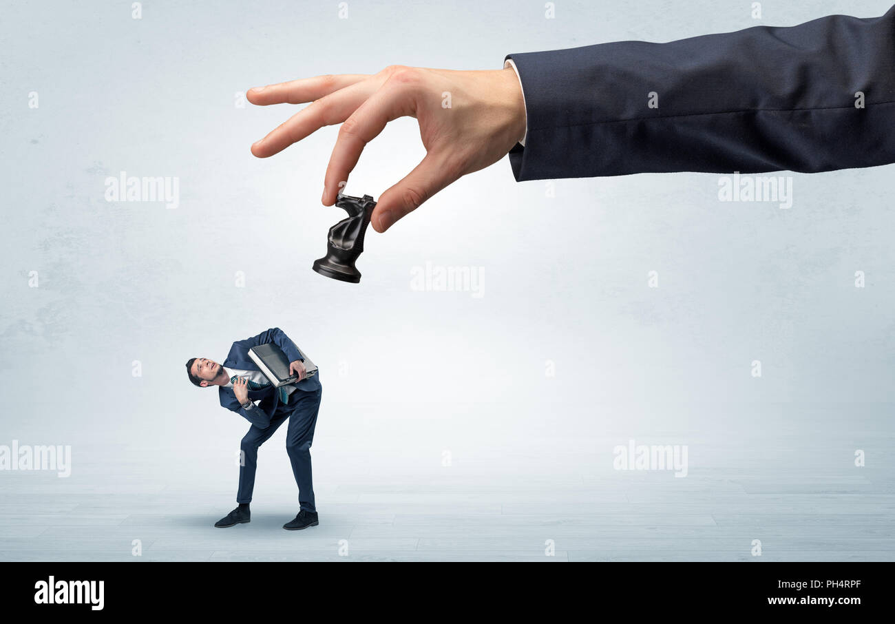 Big hand holding chessman and down little afraid businessman concept in a light space  - Stock Image