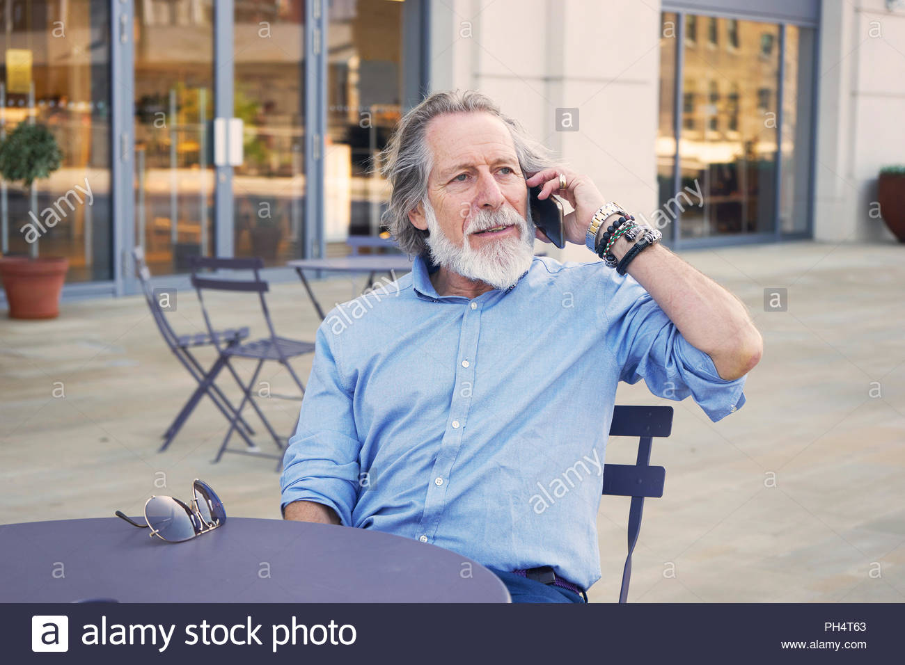 Senior man on phone call at table - Stock Image