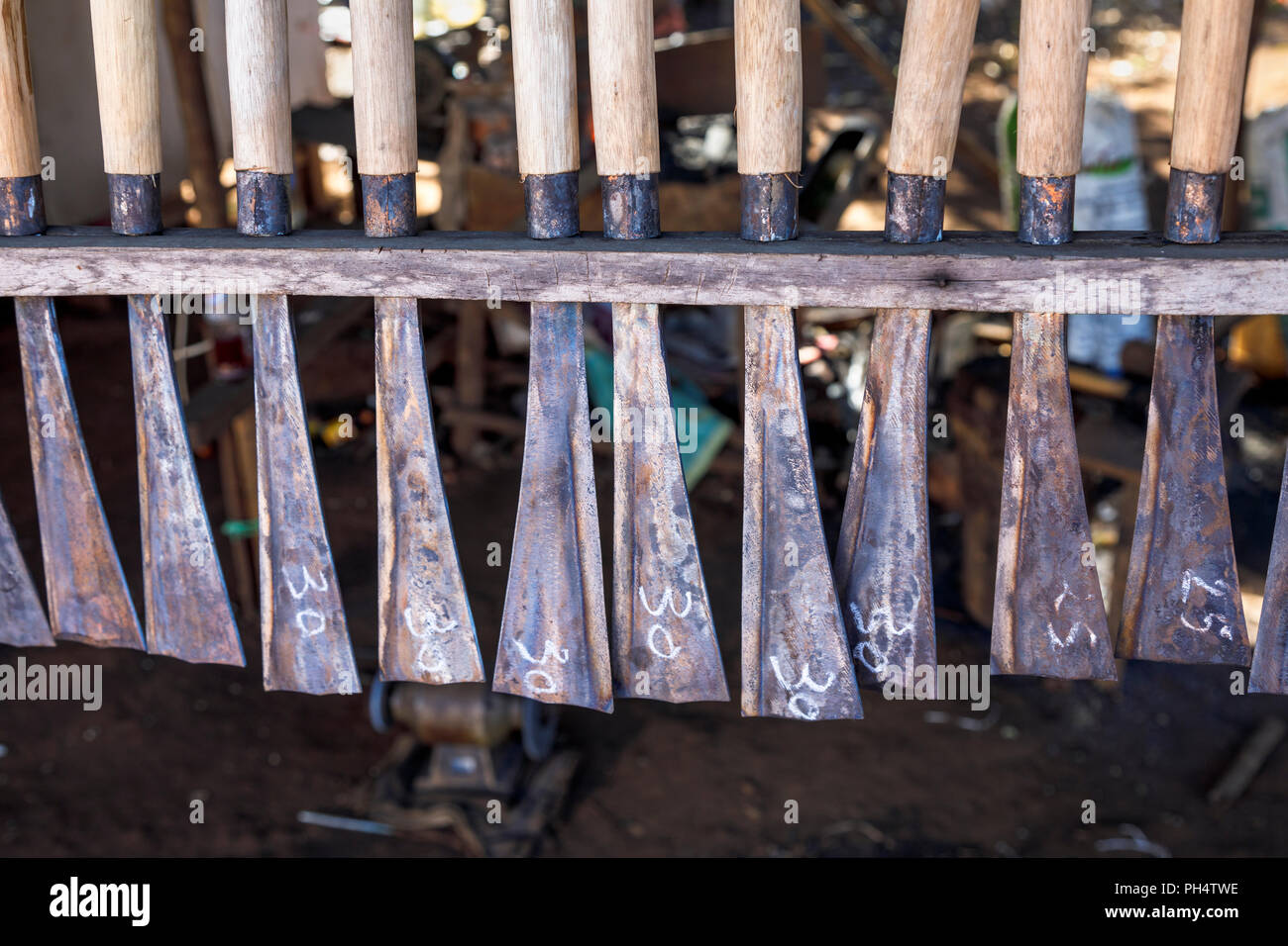 Display of knives and machetes in a roadside stall in Houayhe, a blacksmiths' village in the Bolaven Plateau, Champasak Province, Laos, southeast Asia - Stock Image