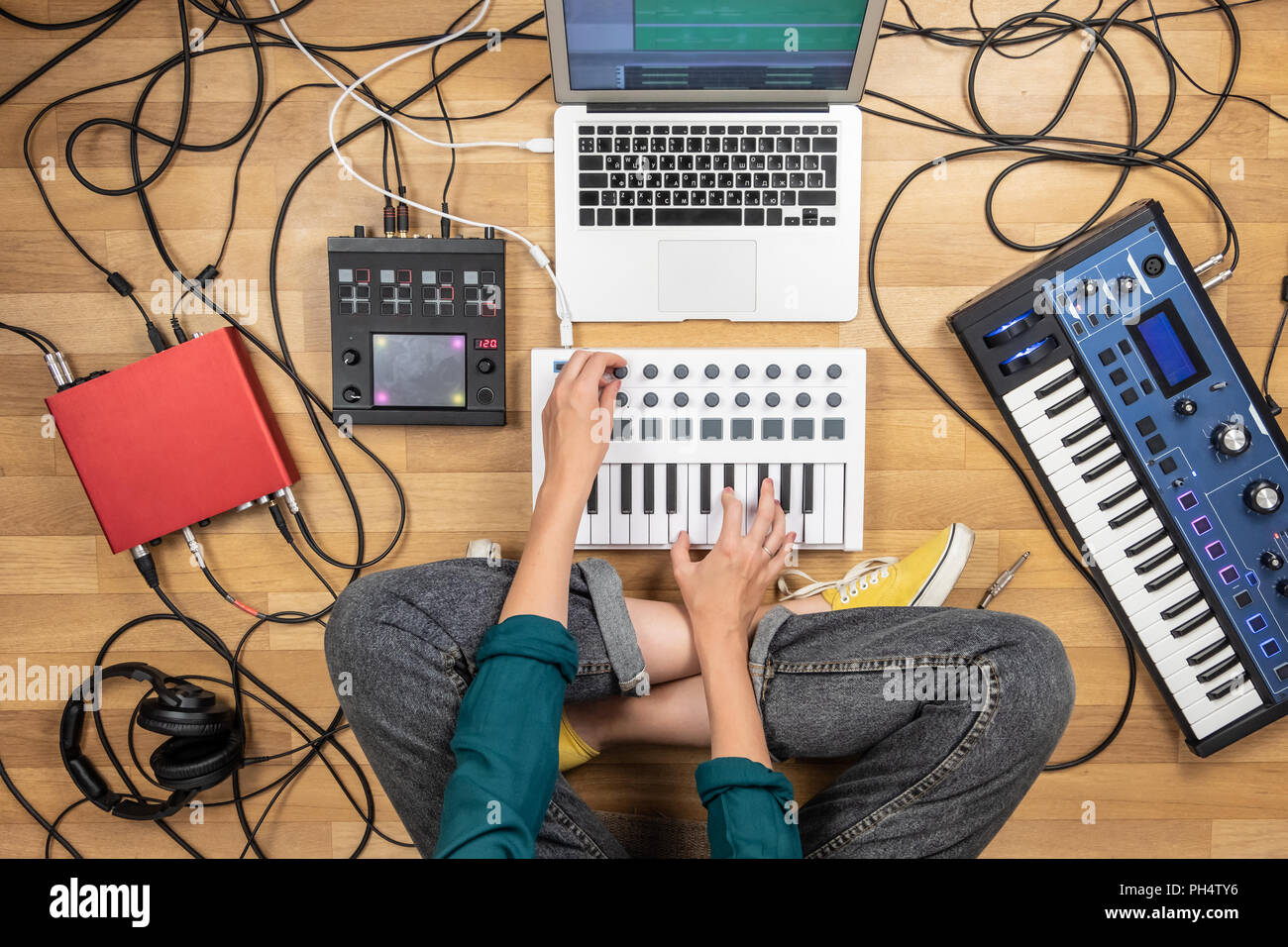 Woman making electronic music on laptop computer and digital instruments. Top view of young female producing modern indie music on synthesizer and dig - Stock Image