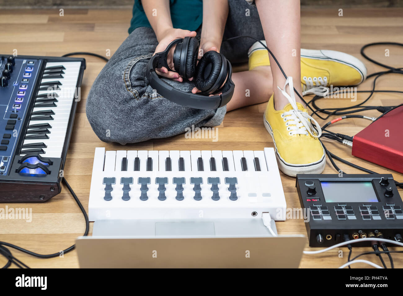 Female musician sits in a home studio with modern electronic instruments. Young woman producing modern indie music on synthesizer and digital controll - Stock Image