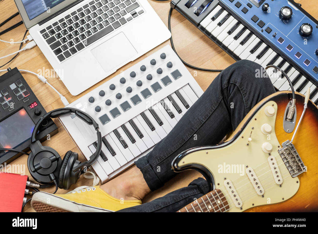 Male guitarist with electric guitar at modern home studio or rehearsal room. Young man producing music with electronic effects processors, synthesizer - Stock Image