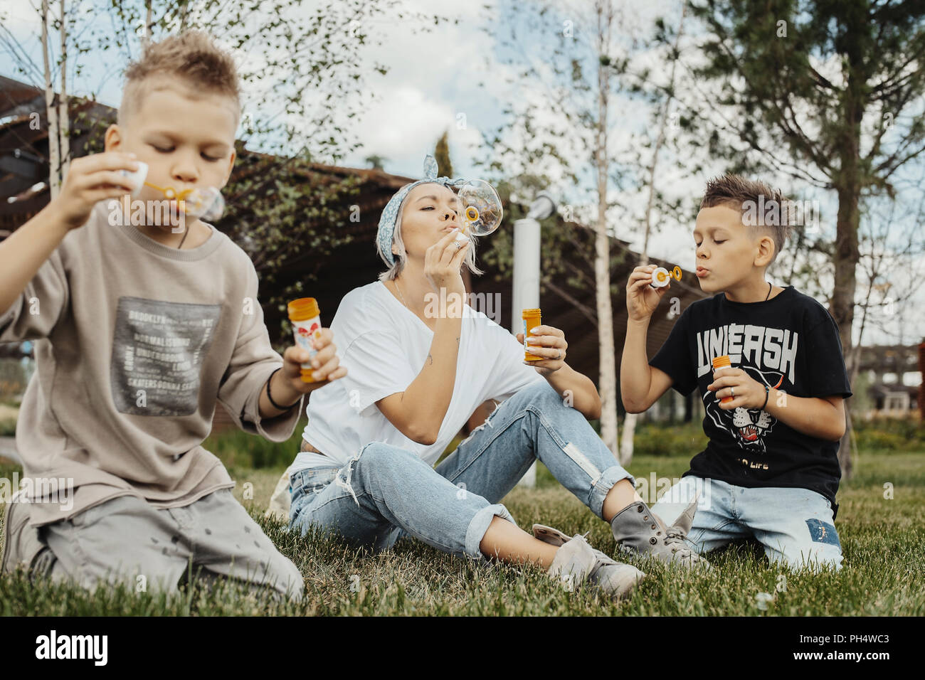 Close up of family blowing bubbles outdoors in the park. - Stock Image