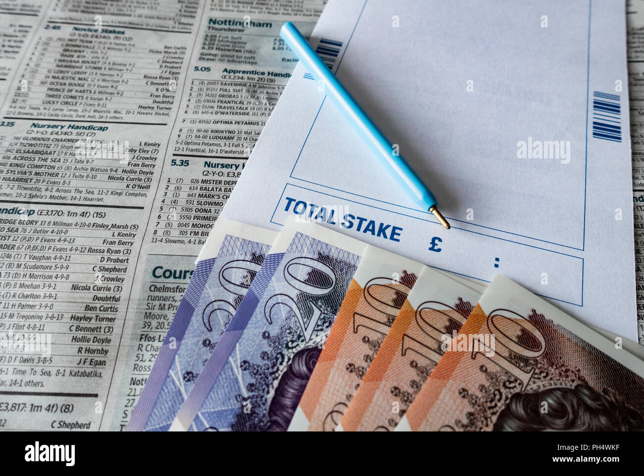 Betting slip with £10 and Twenty pound notes on horse racing page of UK newspaper. - Stock Image