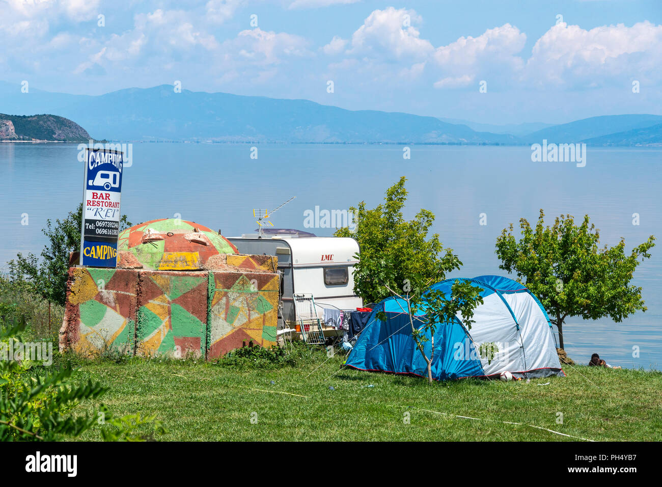 A campsite with painted communist era bunker on the shores of Lake Ohrid at Pogradeci, South eastern Albania. - Stock Image