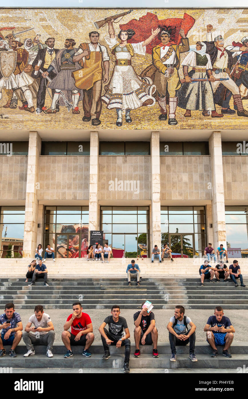 Young people relaxing on the steps of the National Historical Museum, below its, communist era, Mosaic mural, in Skanderbeg Square, Tirana, Albania, - Stock Image