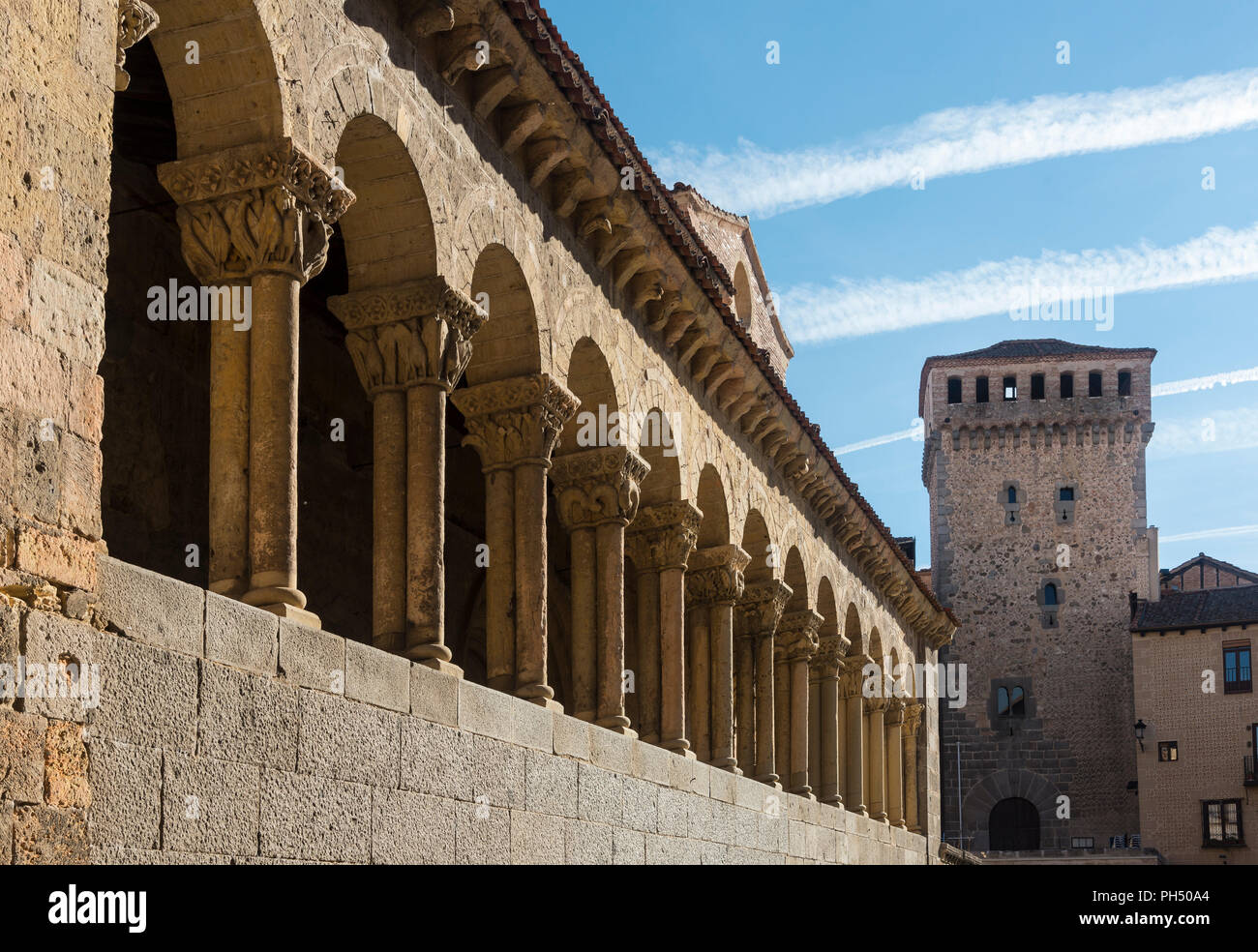 The Romanesque, arcaded portico  of San Martin church, looking towards the Torreón de Lozoya  in the Plaza Medina del Campo, Segovia, Spain - Stock Image
