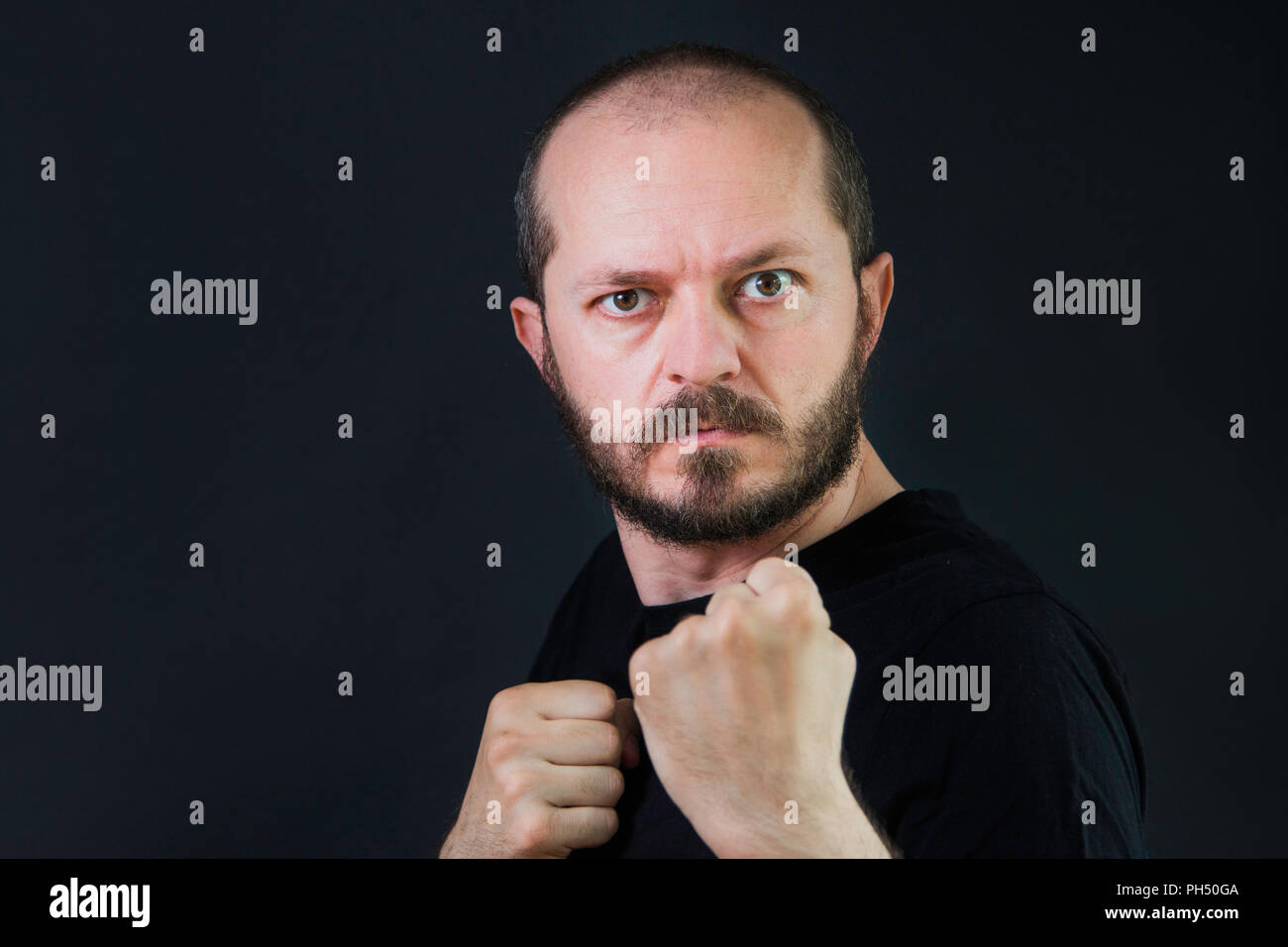 Serious aggressive man with beard and mustaches on black background in low key, holding fists and threatening, ready for fight - Stock Image