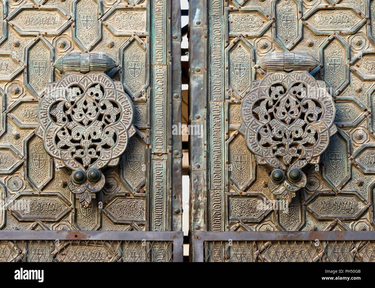 Door knockers on the ornate, bronze, Puerta del Perdon, door of forgivness,  of  the Great Mosque, La Mezquita, in Cordoba, Spain - Stock Image