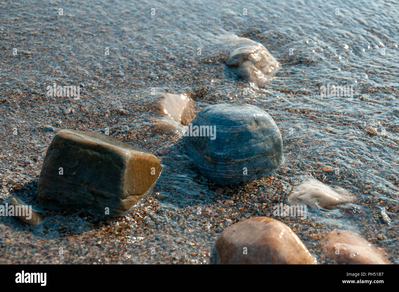 A group of pebbles by the sea shore partly immersed in sea water Stock Photo