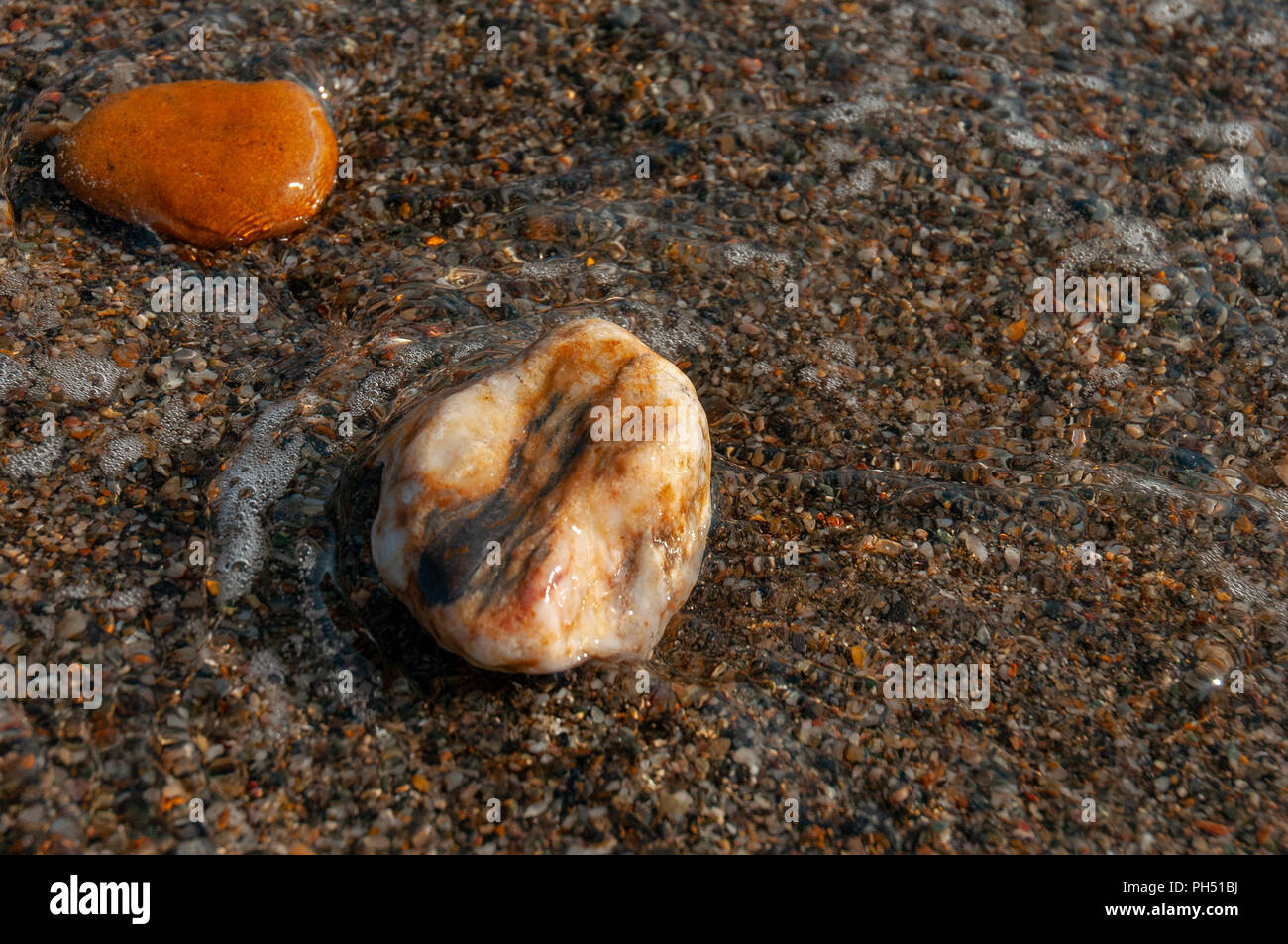 two small wet pebbles near the shoreline partially immersed in the water Stock Photo