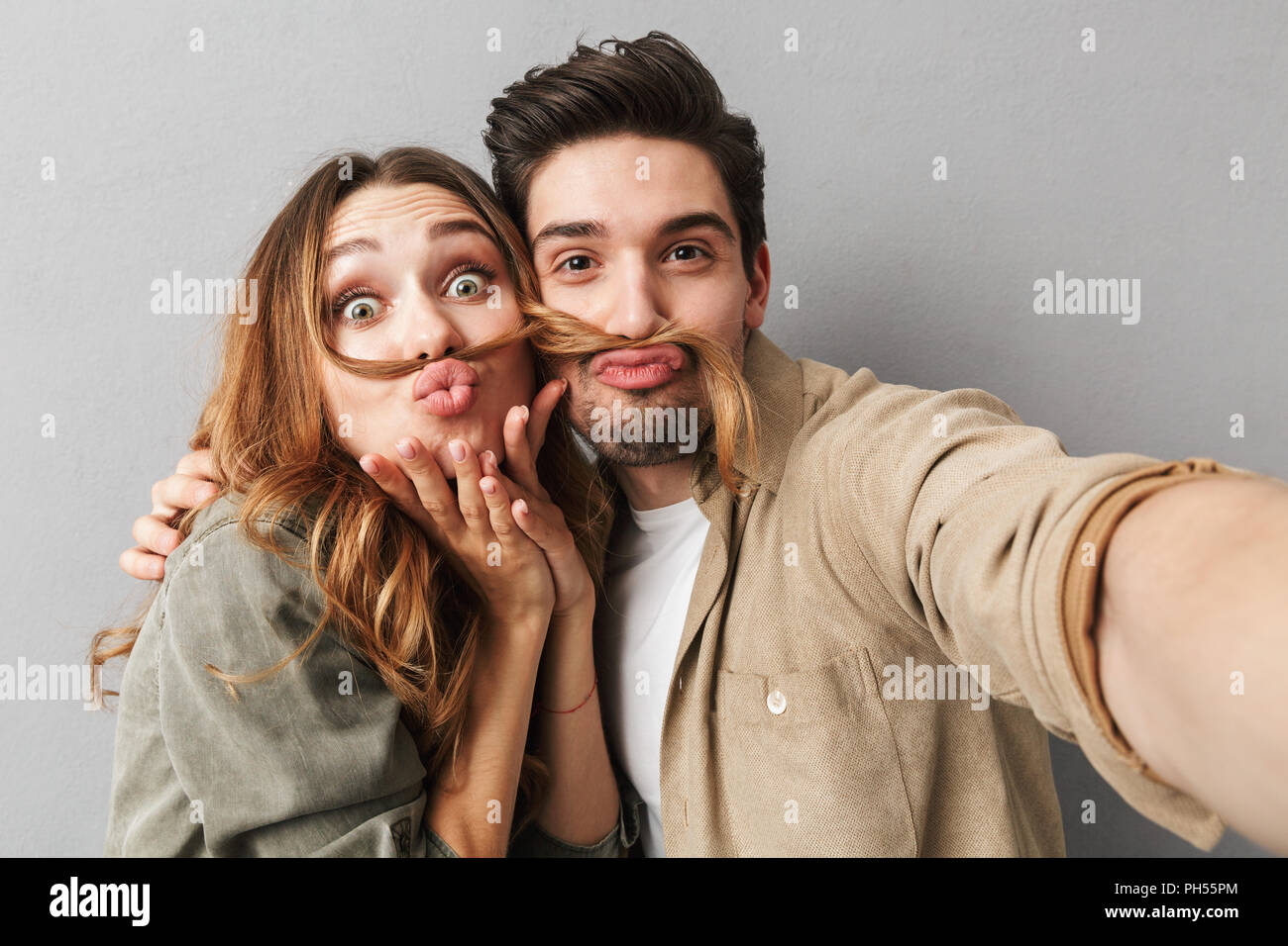 Portrait of a funny young couple hugging while taking a selfie and grimacing isolated over gray background - Stock Image
