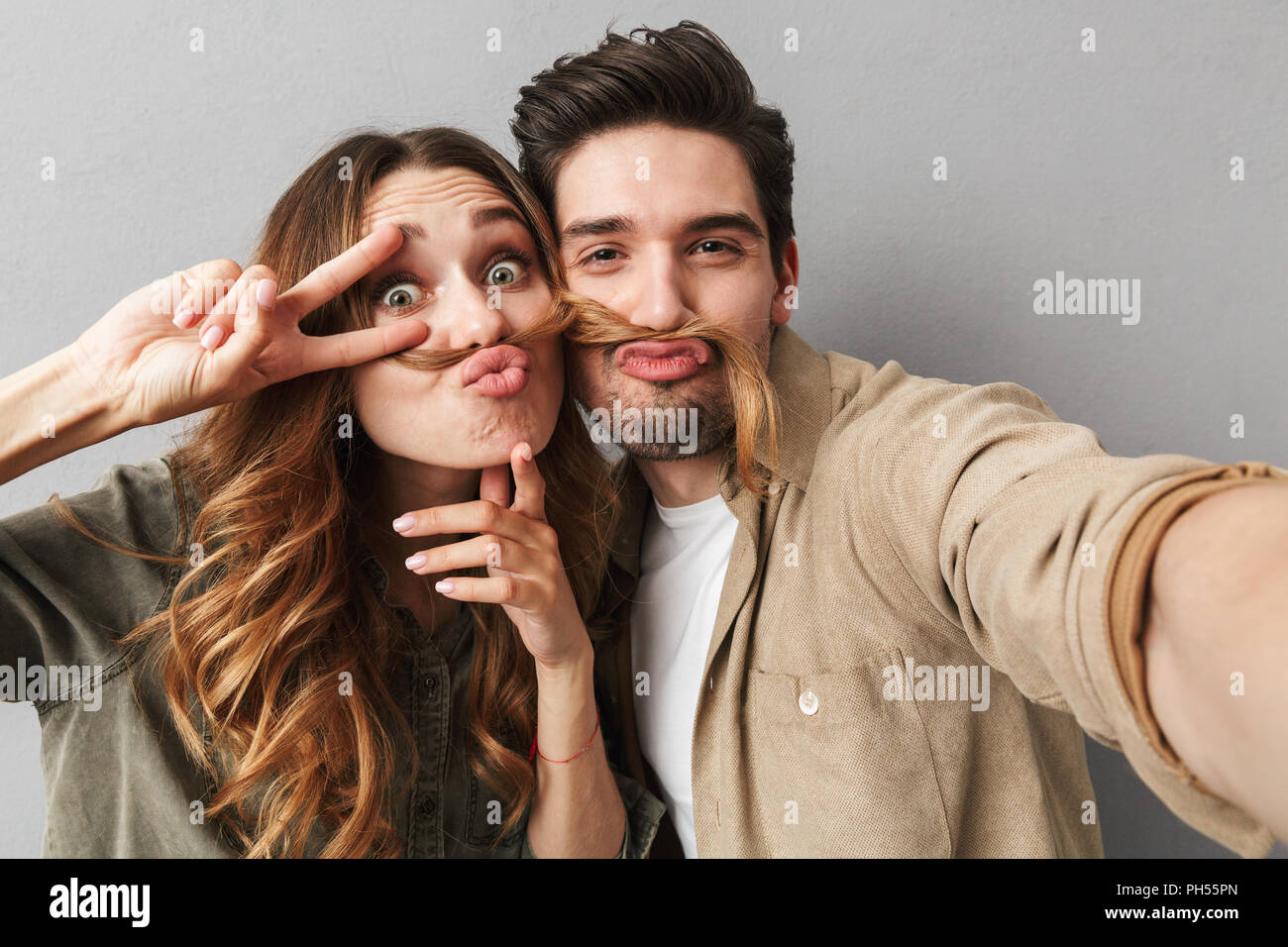 Portrait of a happy young couple hugging while taking a selfie and grimacing isolated over gray background - Stock Image