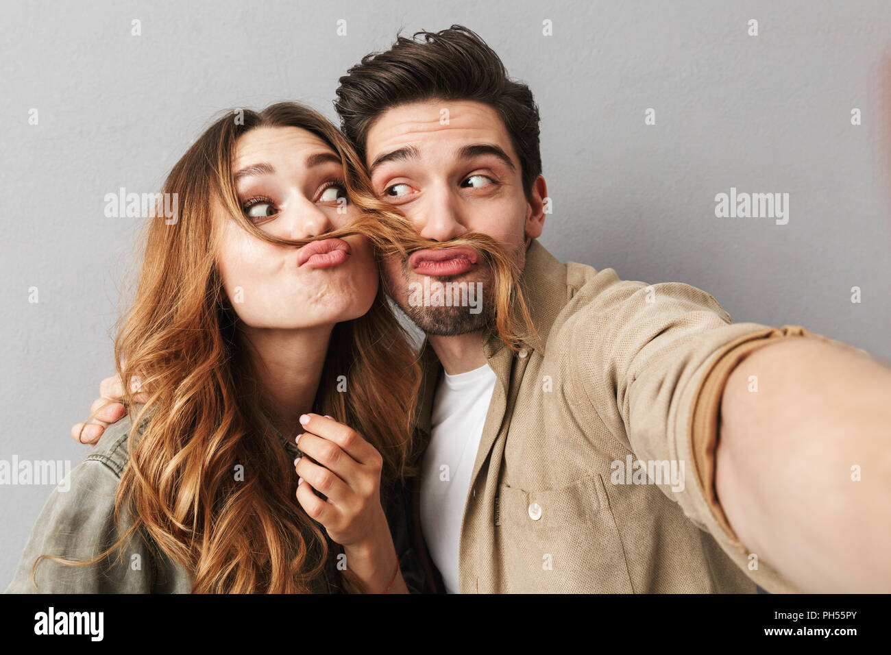 Portrait of a cheerful young couple hugging while taking a selfie and grimacing isolated over gray background - Stock Image
