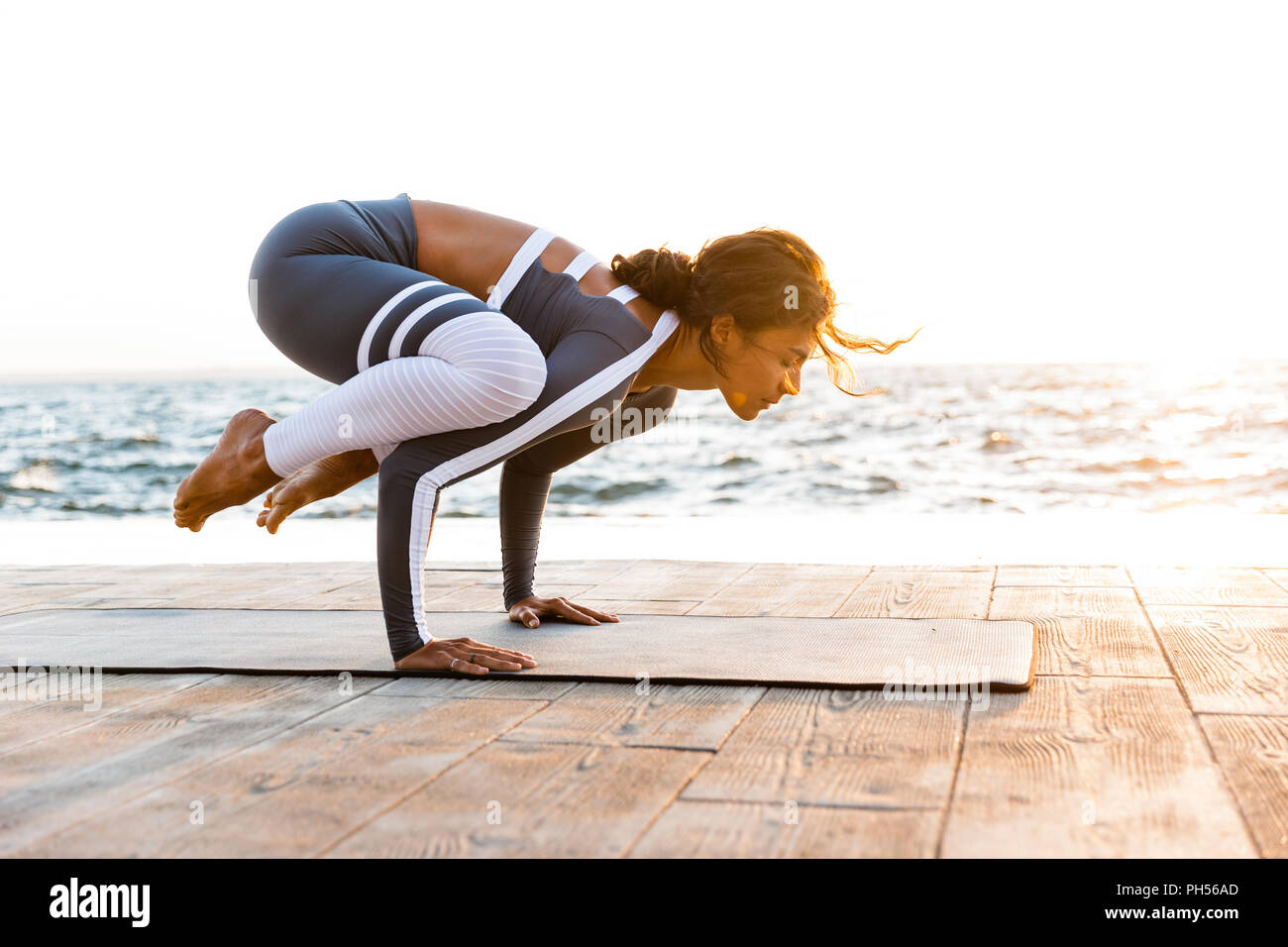 Picture of young fitness lady outdoors in the beach make yoga stretching exercises. - Stock Image