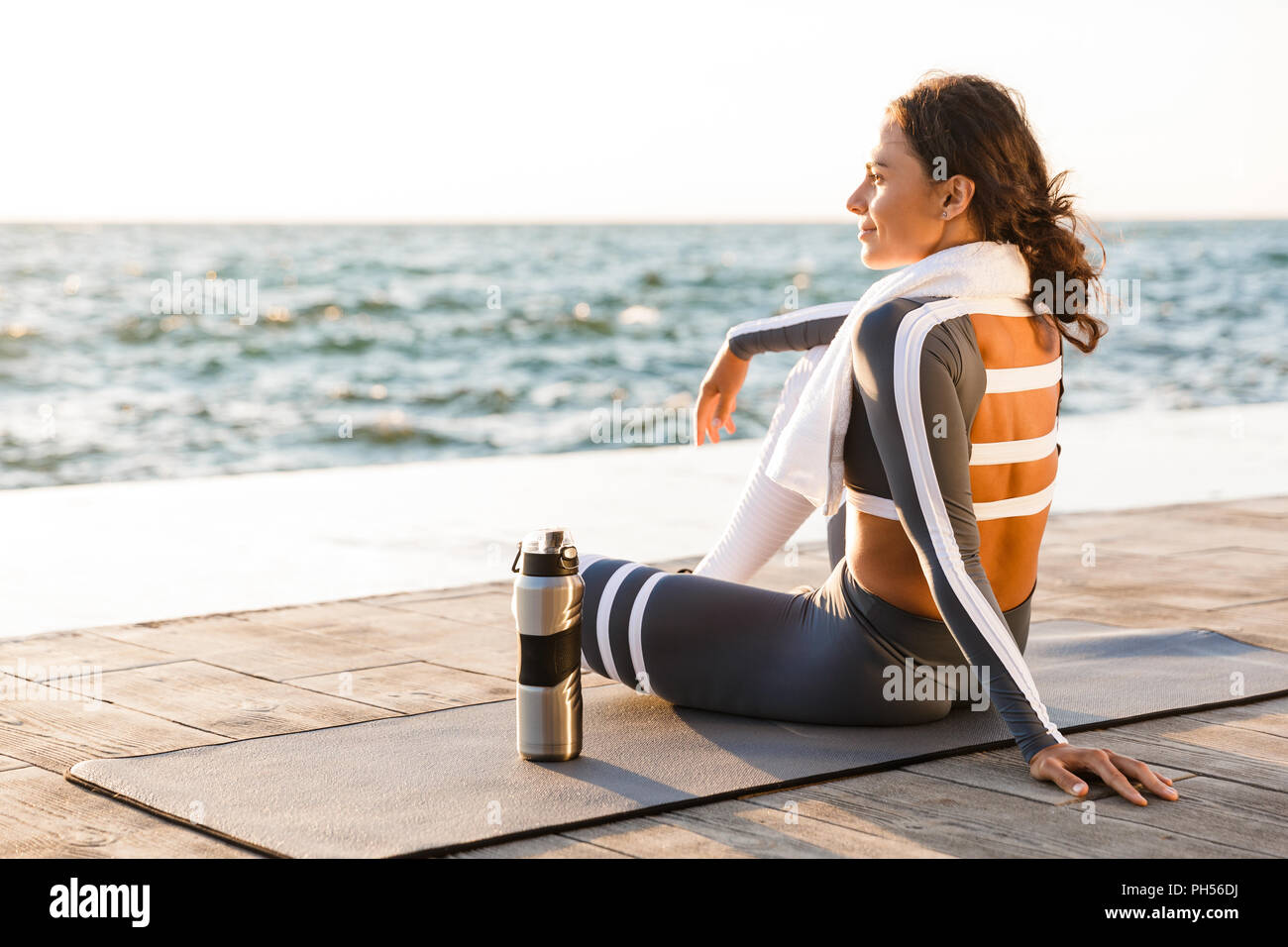 Image of beautiful young fitness woman outdoors on the beach have a rest sitting with towel and water. - Stock Image