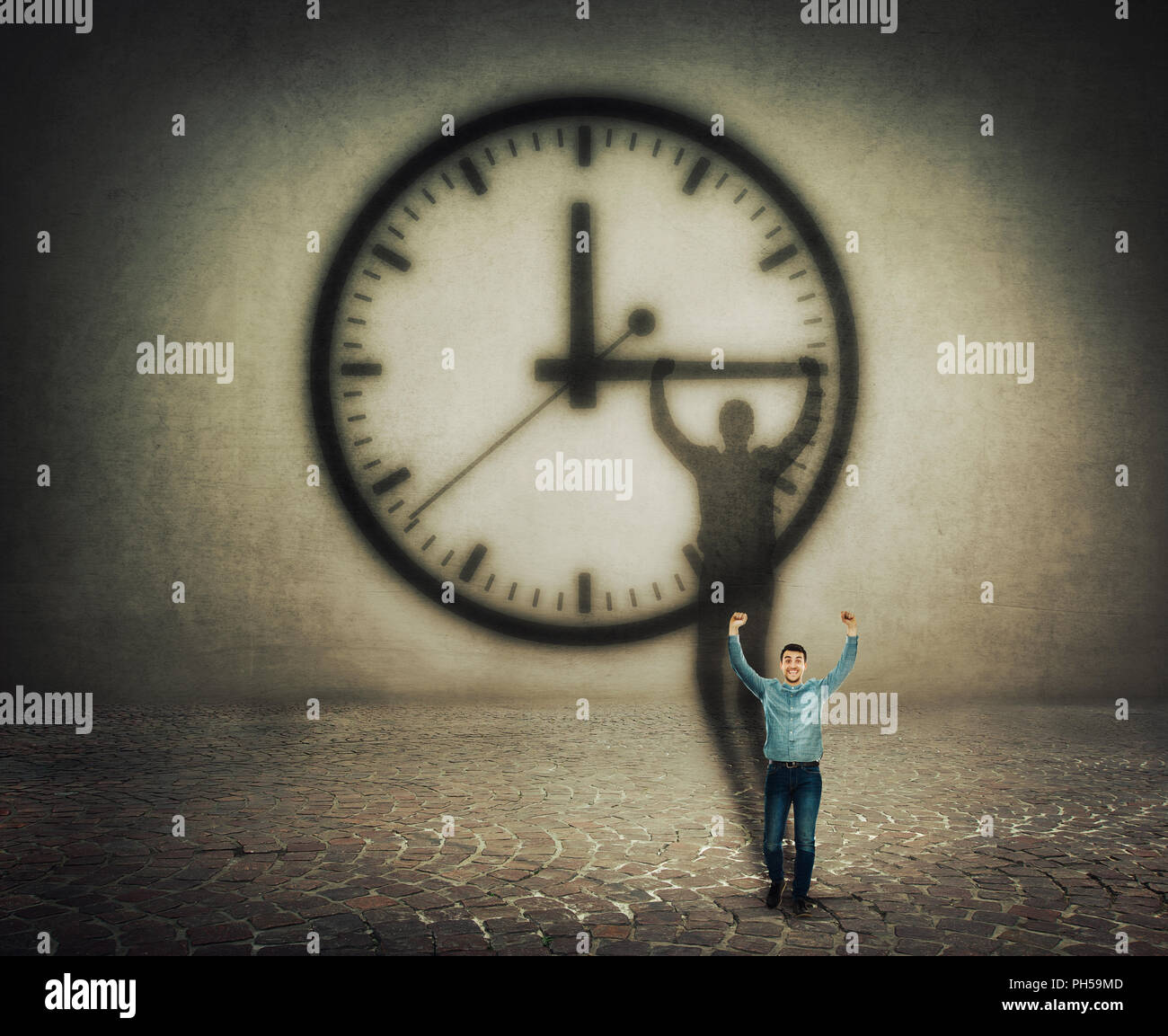 Surreal image of a businessman trying to stop the time. Casting a shadow with hands up holding the clock arrow. - Stock Image