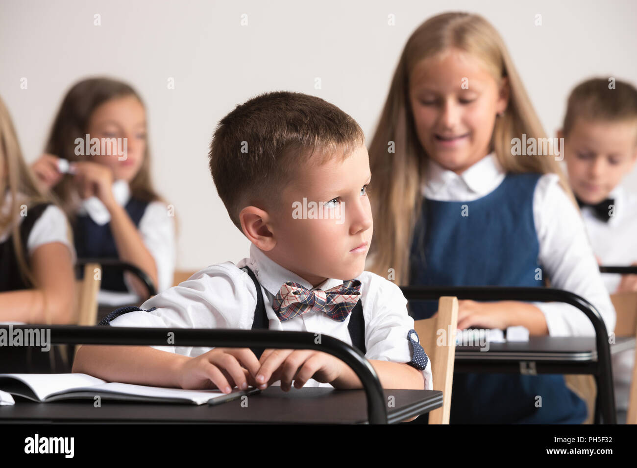 dee0e2f7e20ca School children in classroom at lesson. The little boys and girls sitting  at desks. Back to school, education, classroom, lesson, learn, lifestyle,  ...