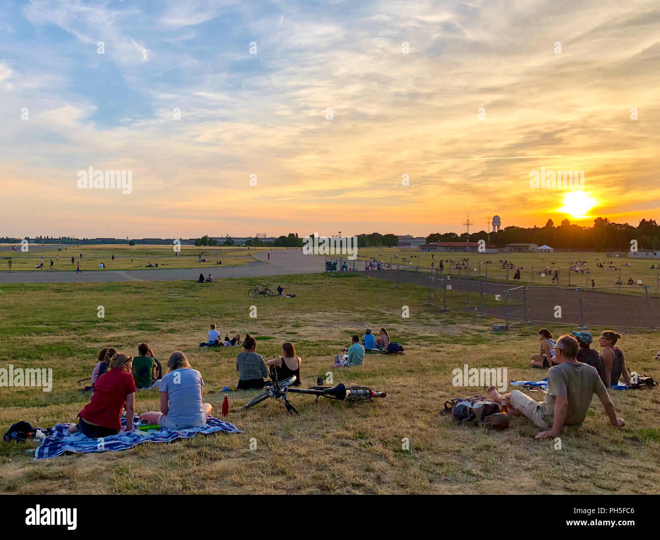 People relaxing and watching a summer sunset at Tempelhofer Feld in Berlin, Germany in 2018. - Stock Image