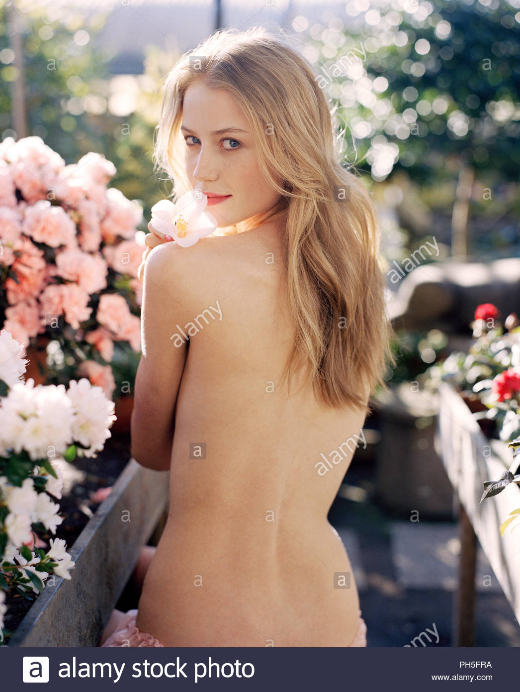 Shirtless young woman in flower garden - Stock Image