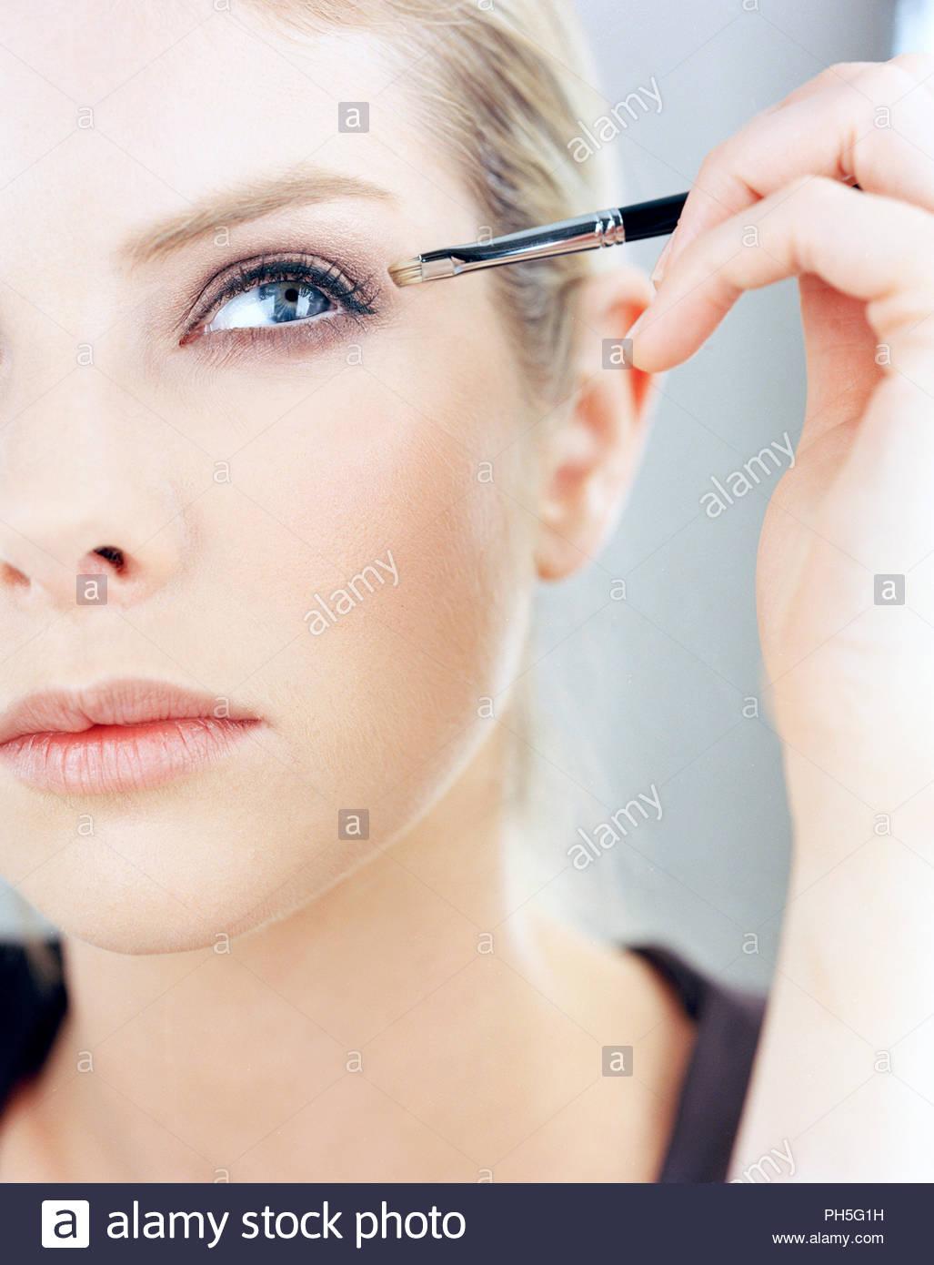 Young woman applying make-up - Stock Image