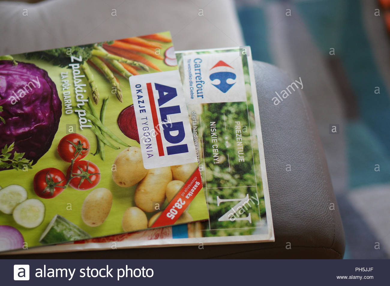 German Aldi and French Carrefour supermarket brochures on a sofa in soft focus - Stock Image
