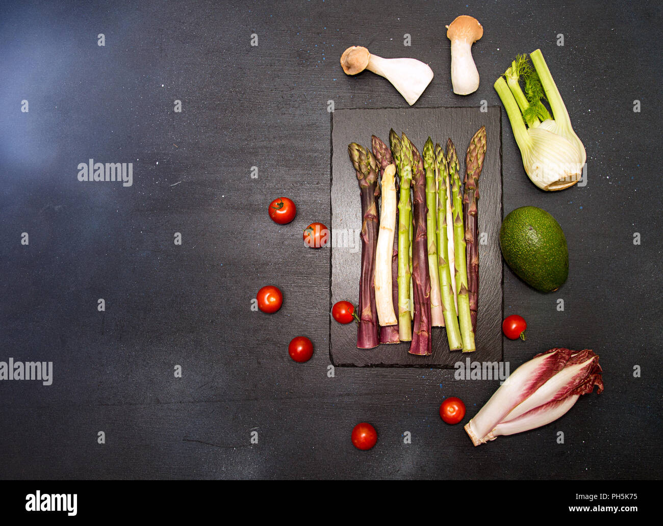 Ingredients for preparing healthy meal. Cherry tomato, asparagus, cherry tomatoes, chicory, fennel, avocado, oyster mushrooms over on black background Stock Photo